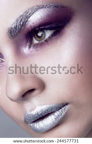 Closeup portrait of a young cute girl over grey background. Perfect bright makeup. Silver lips and eyebrows. Brunette with curly hair. Snow queen. White swan with plumage. Eye and lips. - stock photo