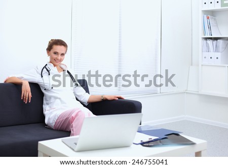Closeup portrait of a young doctor sitting on the sofa - stock photo