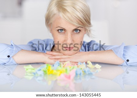 Closeup portrait of a young female executive with colorful crumpled paper balls at desk - stock photo