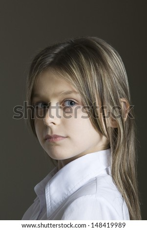 Closeup portrait of a young girl against gray background - stock photo