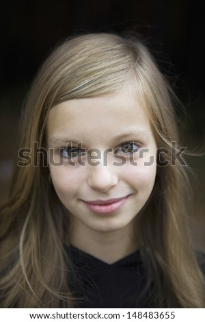 Closeup portrait of a young girl smiling against black background