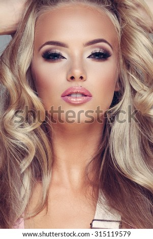 Closeup portrait of a young glamorous lady on grey background - stock photo