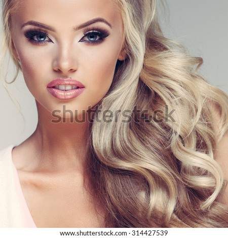 Closeup portrait of a young glamorous lady with beautiful blond hair on grey background - stock photo