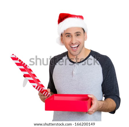 Closeup portrait of a young handsome excited man wearing red santa claus hat, opening gift box and super happy at what he gets, isolated on white background. Positive emotions, facial expressions - stock photo