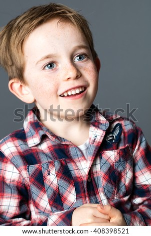closeup portrait of a young male child with blue eyes and freckles laughing for sweet childhood,grey background studio - stock photo