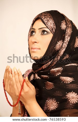 Closeup portrait of a young Muslim woman praying