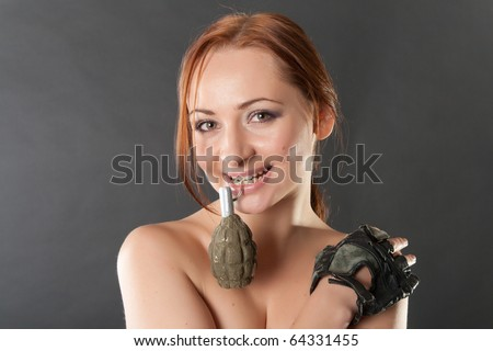 Closeup portrait of a young pretty female model holding the pin of mockup airsoft F-1 grenade in her teeth in studio - stock photo