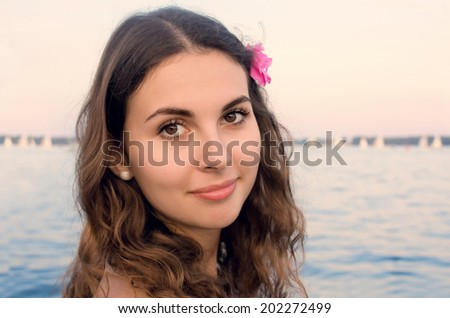 Closeup portrait of a young smiling girl with a pink flower in hair on a beach near the water - stock photo