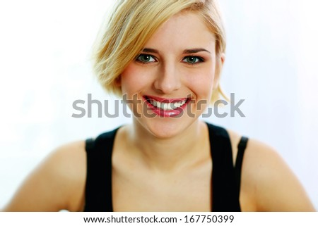 Closeup portrait of a young smiling woman isolated on a white background - stock photo