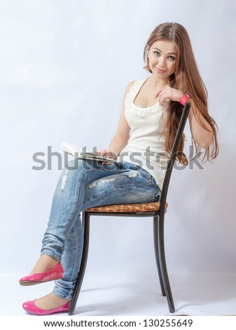 Closeup portrait of a young smiling woman sitting on a chair in jeans reading a book - stock photo