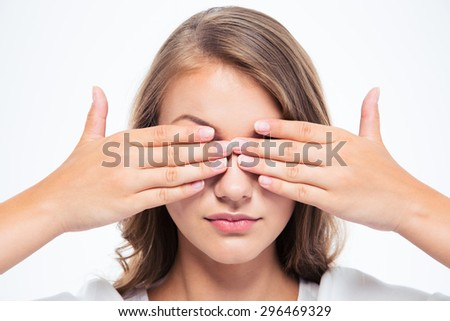 Closeup portrait of a young woman covering her eyes isolated on a white background - stock photo