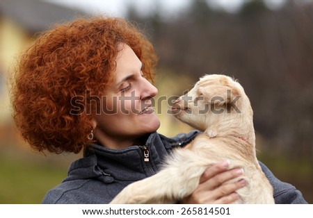 Closeup portrait of a young woman holding a cute baby goat outdoor - stock photo