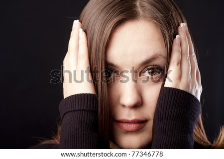 Closeup portrait of a young woman holding her face with hands