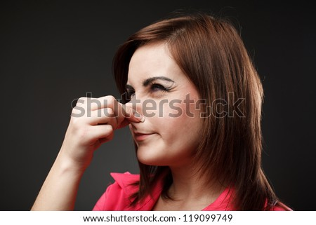 Closeup portrait of a young woman holding her nose because of a bad smell - stock photo