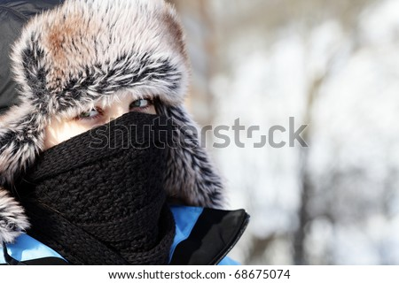 Closeup portrait of a young woman in fur hat and winter cloths outdoors - stock photo