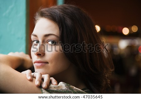 Closeup portrait of a young woman resting her arms on a windowsill. Horizontal shot.