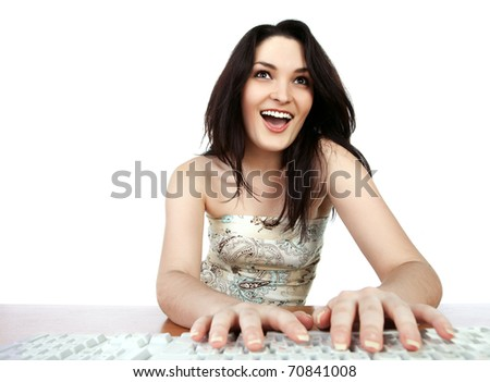 Closeup portrait of a young woman sitting on table and using a computer - stock photo