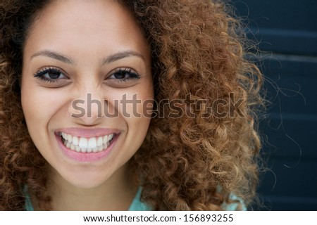 Closeup portrait of a young woman smiling with happy expression on face - stock photo