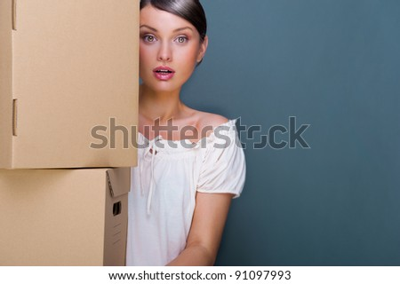 Closeup portrait of a young woman with boxes - stock photo