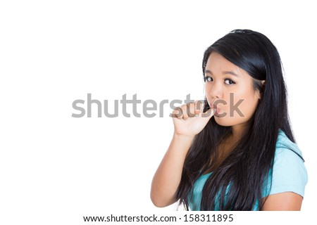 Closeup portrait of a young woman with finger in mouth sucking thumb or biting fingernail in anxiety,stress, or bored and clueless about situation isolated on white background with copy space.