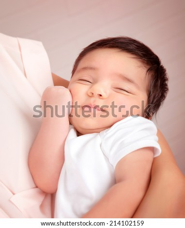 Closeup portrait of adorable Arabic child sleeping on mothers hands, little innocent baby, peace and harmony concept - stock photo