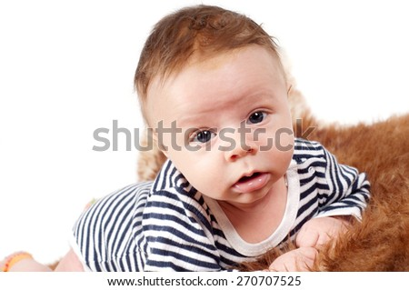 Closeup portrait of adorable baby boy lying on fur watching on you - stock photo