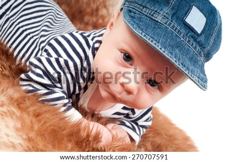 Closeup portrait of adorable baby in cap lying on fur - stock photo
