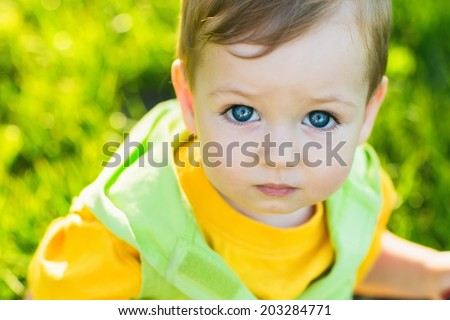 Closeup portrait of adorable blue-eyed baby looking at camera - stock photo