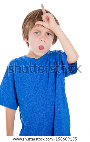 Closeup portrait of adorable kid gesturing loser sign on forehead while sticking tongue out at you or the camera, isolated on white background - stock photo