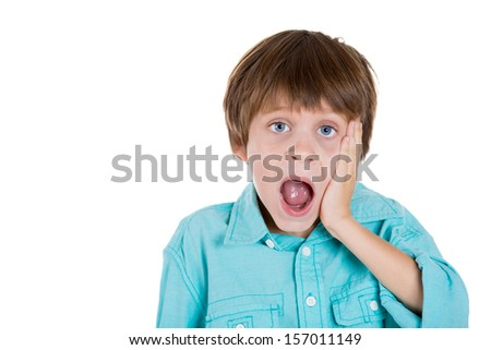 Closeup portrait of adorable kid with hand on cheek and jaw dropped, looking surprised, shocked, and scared, isolated on white background with copy space