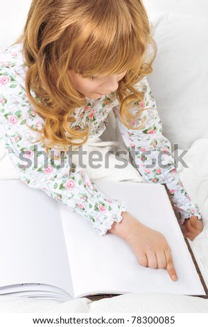 Closeup portrait of adorable little girl resting in her bed with white with beautiful long curly hair