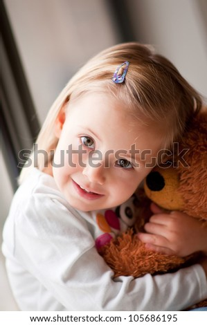 Closeup portrait of adorable toddler girl cuddling with a teddy bear - stock photo