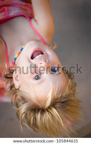 Closeup portrait of adorable toddler girl hanging upside down - stock photo
