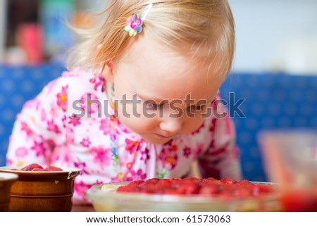 Closeup portrait of adorable toddler girl with ready to bake strawberry pie