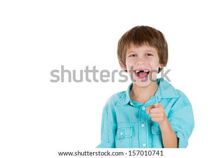 Closeup portrait of adorable young boy, pointing and laughing at you, isolated on white background with copy space
