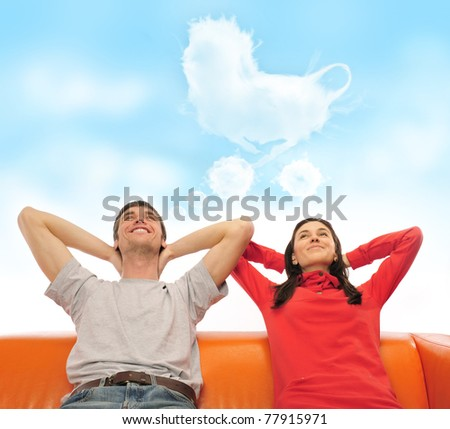 Closeup portrait of adult couple sitting on their sofa and dreaming about pregnancy and baby. Blank balloon at the top of the photo for your text. Planning future happy family concept