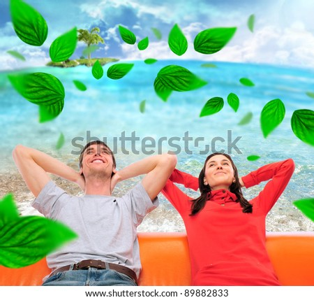 Closeup portrait of adult couple sitting on their sofa at their apartment and dreaming about something. Planning future concept Green leaves are floating around them - stock photo