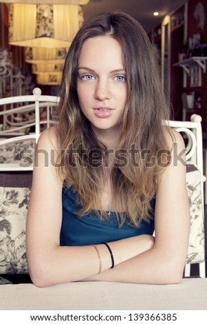 Closeup portrait of an amazing fresh young woman sitting at the cafe with hands crossed in blue dress with blue eyes looking awesome - stock photo