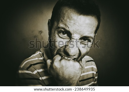 Closeup portrait of an angry guy biting his fist, looking at the camera. Old sepia style picture. - stock photo