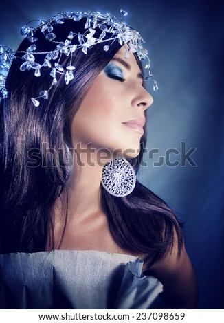 Closeup portrait of an attractive female with closed eyes and perfect festive makeup over blue background, wearing fashionable accessories, Christmas party concept - stock photo