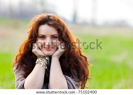 Closeup portrait of an attractive young lady outdoor on a meadow