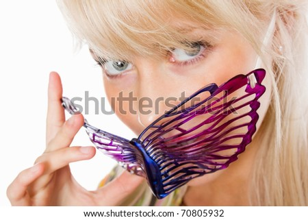 Closeup portrait of an attractive young woman holding party mask - stock photo