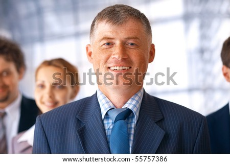 Closeup portrait of an elder businessman in front of his team. - stock photo