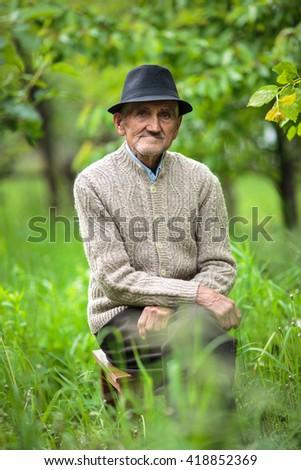 Closeup portrait of an elderly man outdoor in the garden - stock photo