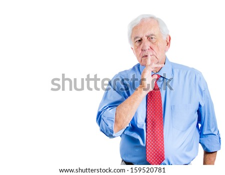 Closeup portrait of an elderly man, serious old corporate executive placing finger on lips as if to say, shhhhh, be quiet, silence, and looking at you, isolated on white background with copy space - stock photo
