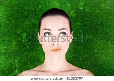 Closeup portrait of an expressive thoughtful woman looking up in studio against green - stock photo