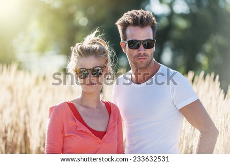 closeup portrait of an handsome couple outside, they wear sunglasses - stock photo