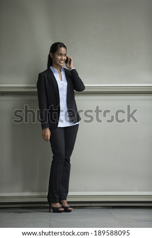 Closeup Portrait of an Indian businesswoman standing outside using mobile phone - stock photo