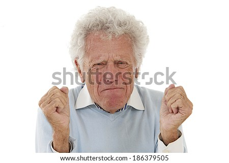 Closeup portrait of an old man, grandfather,   blue  pull over yelling at someone with fists in the air, looking very unhappy, mad and angry, isolated on white background  - stock photo