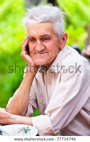 Closeup portrait of an old man outdoor, smiling - stock photo